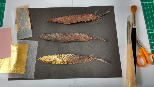 Gold leaf applied to embroidered paper